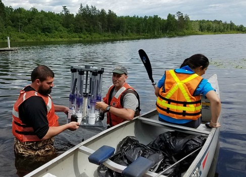 Scientists deploying a device to collect pore-water samples from different depths in lake sediments.